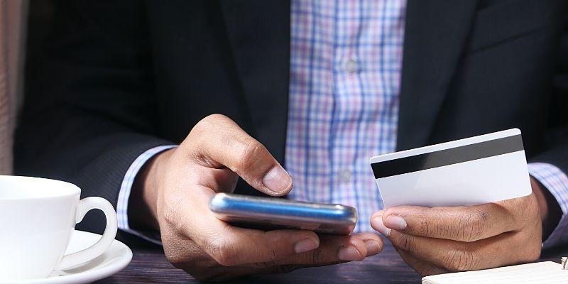 Uomo d'affari con cellulare e carta di credito in mano